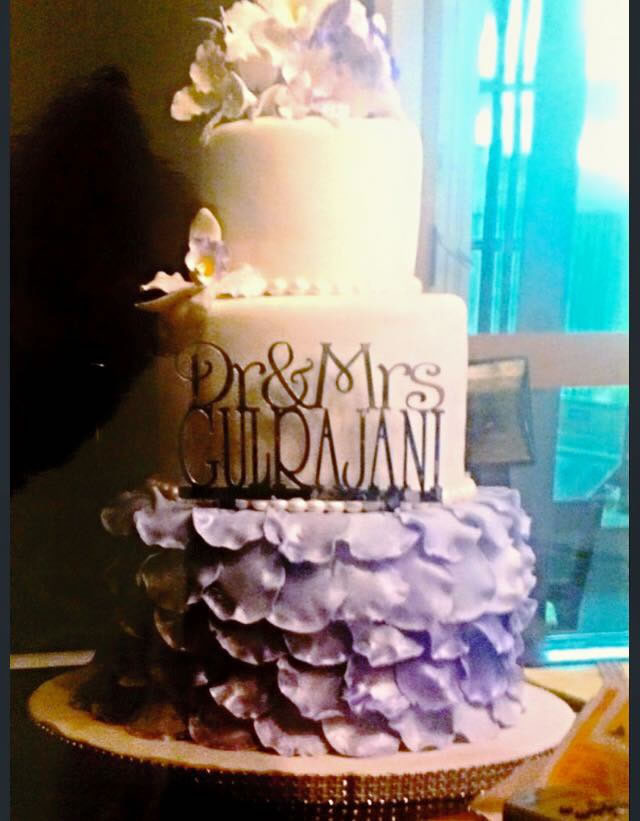 White Fondant With Bunches Of Sugar Flowers And Petals Cover This 3 Tier Round Wedding Cake